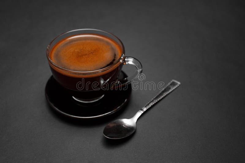 Zwarte, natuurlijke, geurige koffie in de transparante kop op een zwarte achtergrond stock foto's
