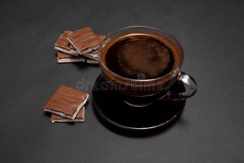 Zwarte, natuurlijke, geurige koffie in de transparante kop op een zwarte achtergrond, met melkchocola royalty-vrije stock afbeelding