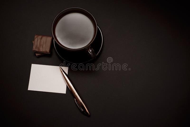 Zwarte, natuurlijke, geurige koffie in de transparante kop op een zwarte achtergrond, met melkchocola stock foto