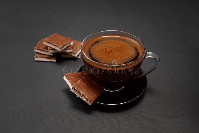 Zwarte, natuurlijke, geurige koffie in de transparante kop op een zwarte achtergrond, met melkchocola stock afbeelding