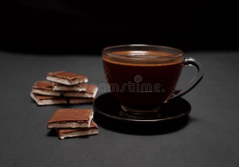 Zwarte, natuurlijke, geurige koffie in de transparante kop op een zwarte achtergrond, met melkchocola stock afbeeldingen