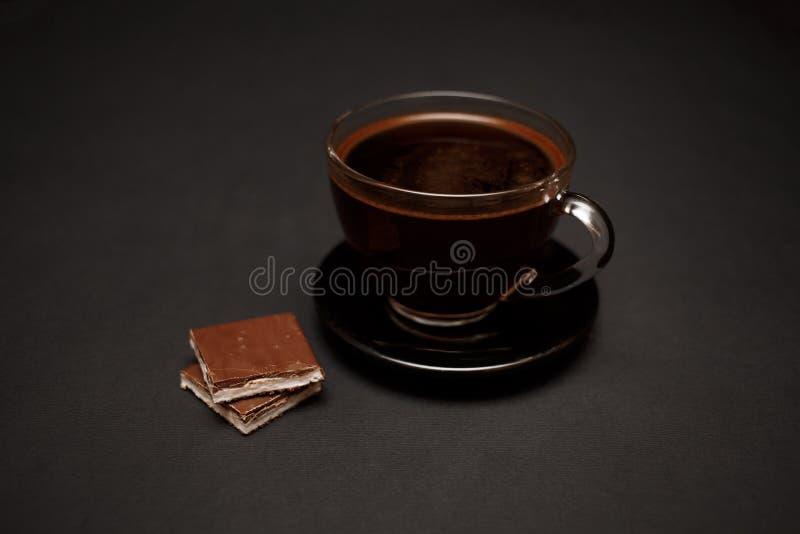 Zwarte, natuurlijke, geurige koffie in de transparante kop op een zwarte achtergrond, met melkchocola royalty-vrije stock foto's