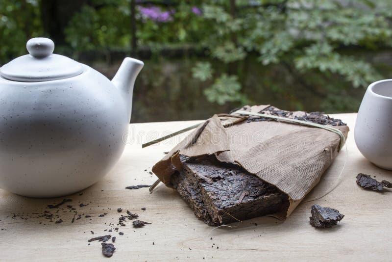 Zwarte natuurlijke thee met witte waterketel en een kop op de houten lijst royalty-vrije stock fotografie