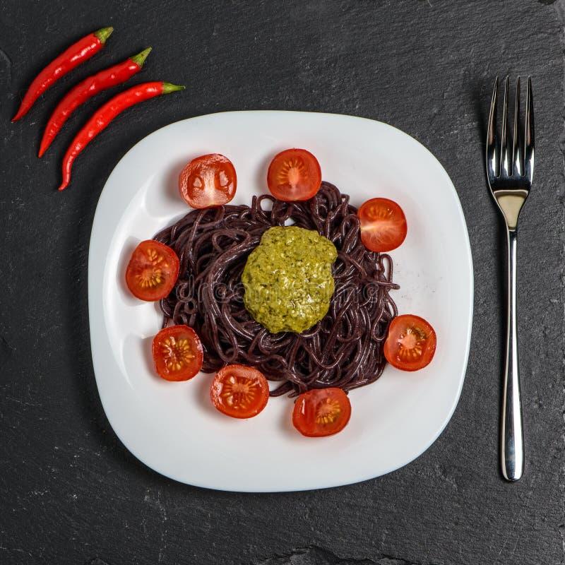 Zwarte noedels met tomaten en pestosaus royalty-vrije stock fotografie