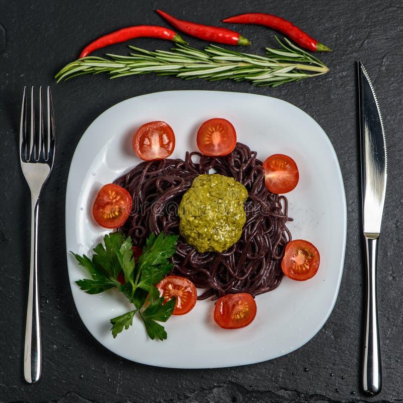 Zwarte noedels met tomaten, en pestosaus royalty-vrije stock afbeeldingen
