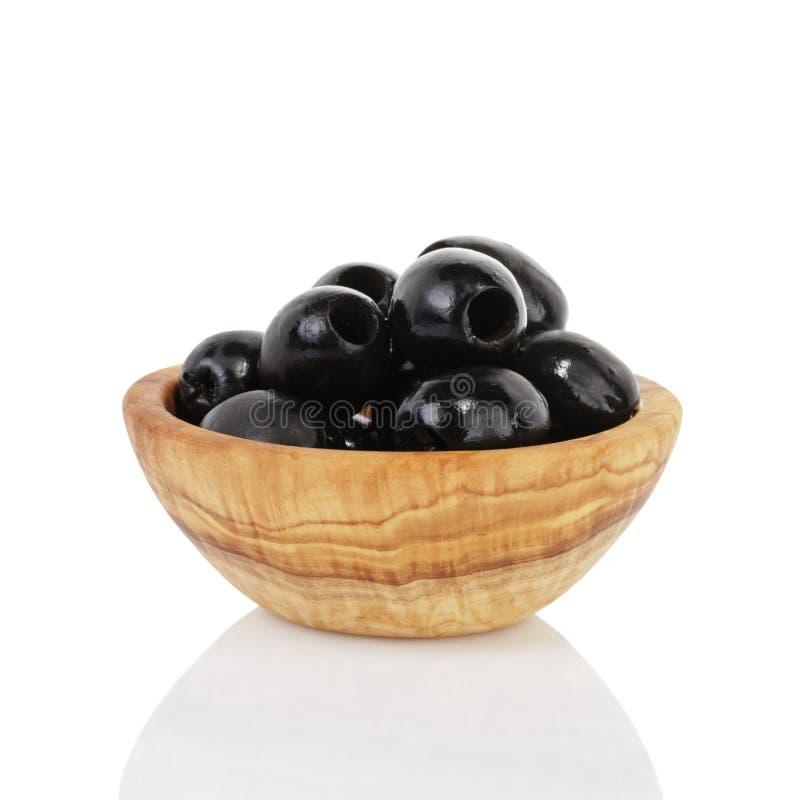 Zwarte olijven in houten die kom, op wit wordt geïsoleerd stock foto