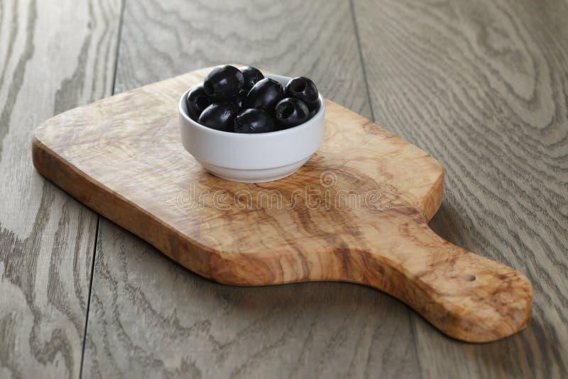 Zwarte olijven in kom op lijst stock foto's