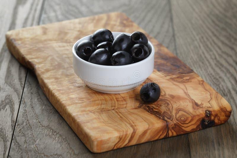Zwarte olijven in kom op lijst stock afbeeldingen