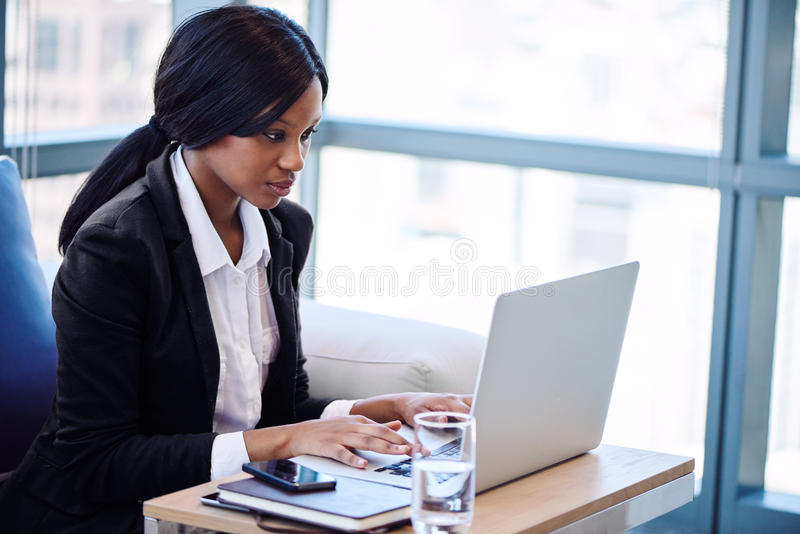 Zwarte onderneemster die aan haar notitieboekje in een bedrijfszitkamer werken stock afbeelding