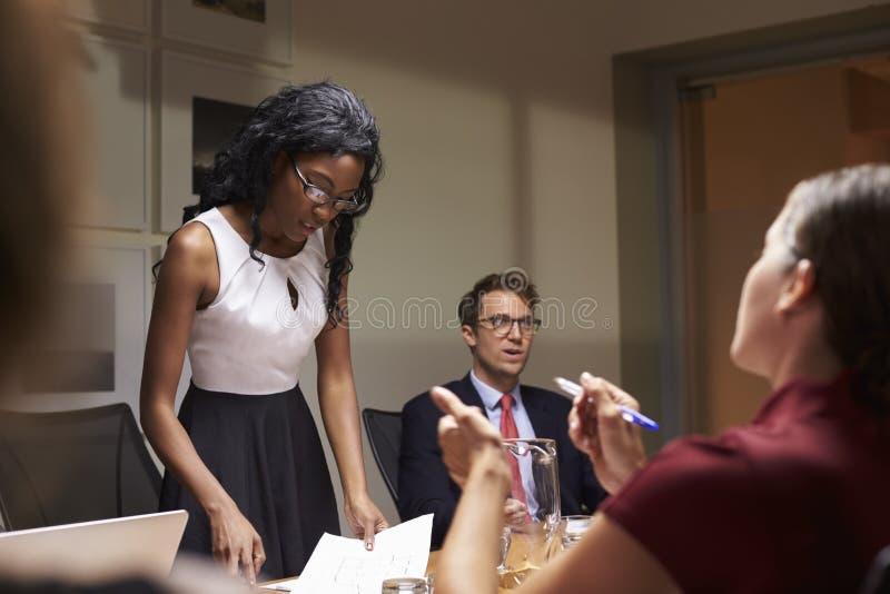 Zwarte onderneemster die aan team op vergadering, lage hoek lezen stock foto's