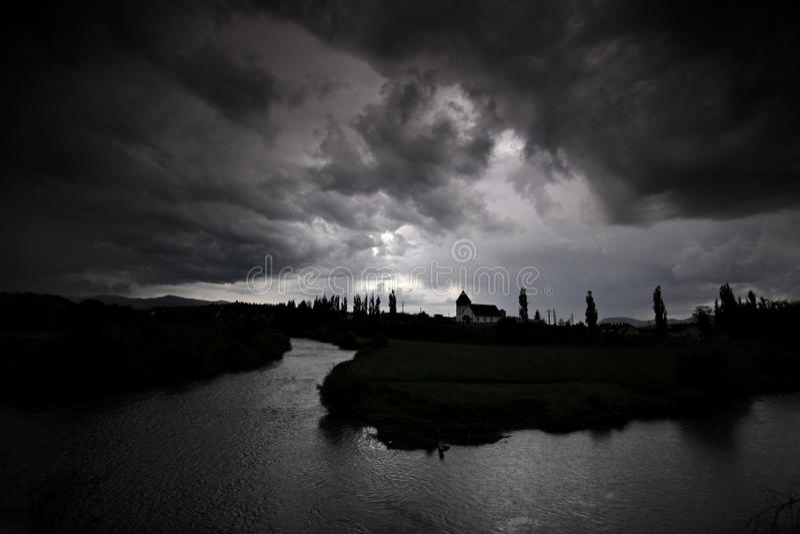 Zwarte onweerswolken over een rivier stock foto