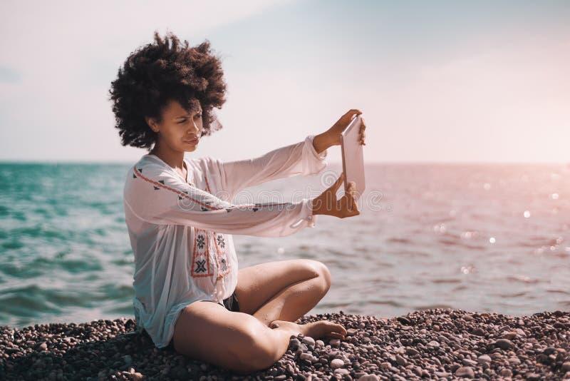 Zwarte op strand die selfie op haar digitale tablet nemen royalty-vrije stock afbeelding