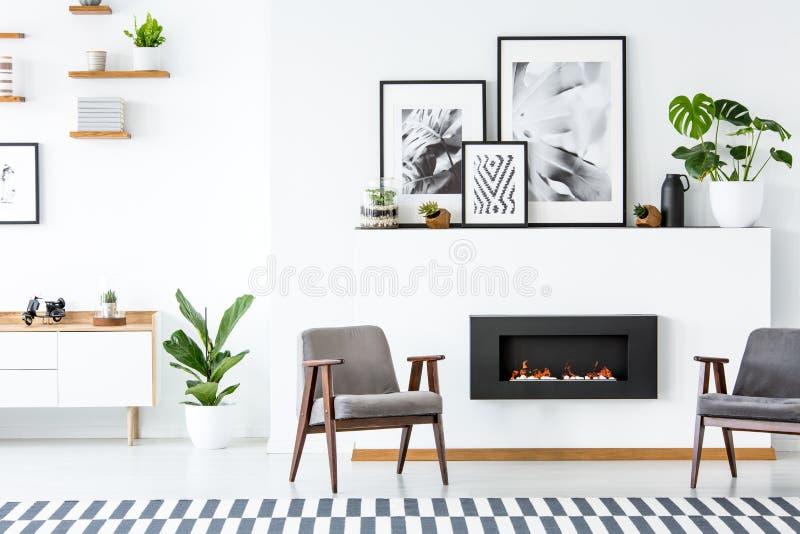 Zwarte open haard tussen grijze leunstoelen in flat binnenlands verstand royalty-vrije stock foto's