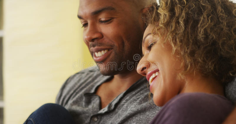 Zwarte paarzitting bij laag het glimlachen royalty-vrije stock foto
