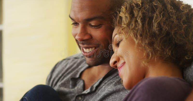 Zwarte paarzitting bij laag het glimlachen royalty-vrije stock afbeelding