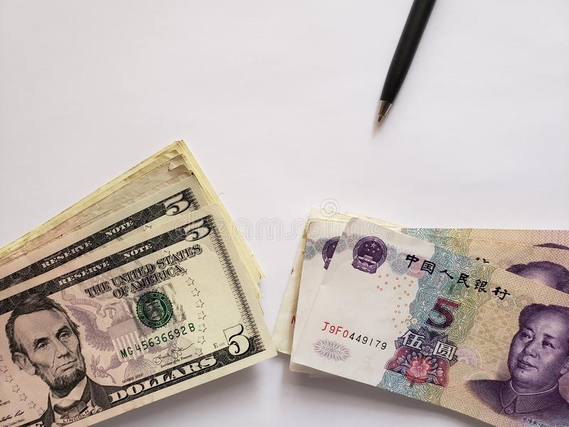 zwarte pen, Chinese bankbiljetten, Amerikaanse dollarrekeningen en witte achtergrond royalty-vrije stock afbeeldingen