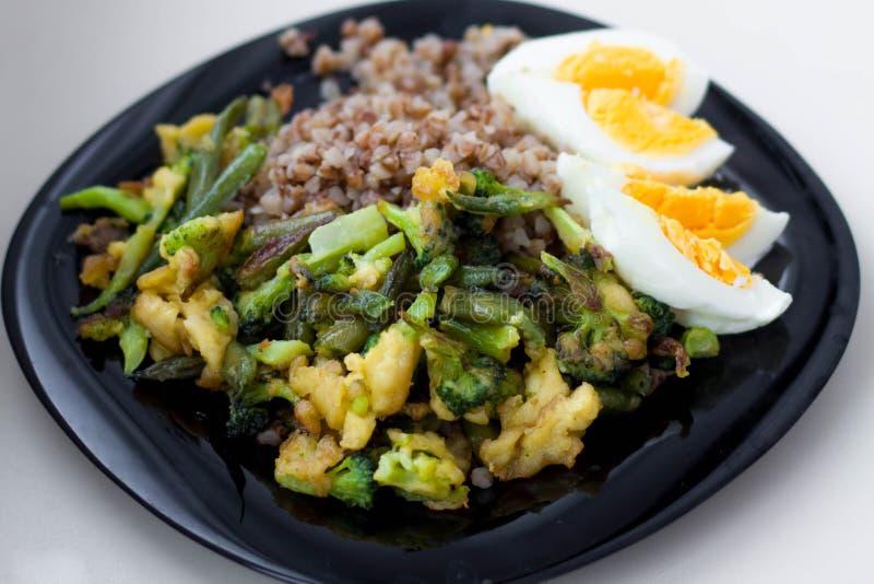 Zwarte plaat met boekweit en groenten, broccoli royalty-vrije stock afbeeldingen