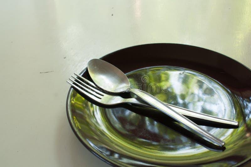Zwarte plaat met lepel en vork stock fotografie
