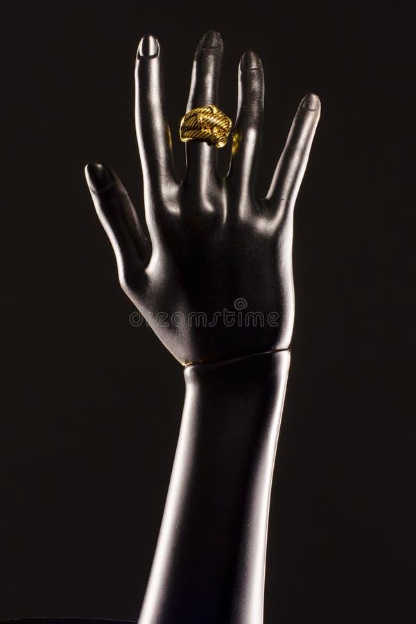 Zwarte plastic hand van een ledenpop op een zwarte achtergrond met een gouden ring op haar vinger stock afbeelding