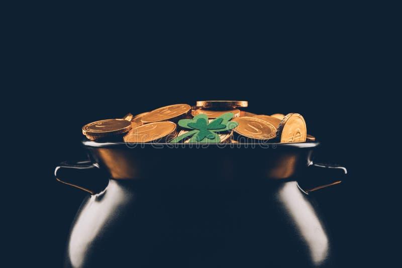zwarte pot met gouden die muntstukken op zwarte, st patricks dagconcept worden geïsoleerd royalty-vrije stock afbeeldingen