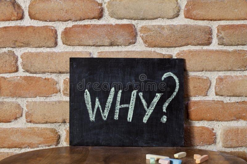 Zwarte raad met het woord WAAROM? verdrink met de hand op houten lijst aangaande bakstenen muurachtergrond stock afbeeldingen