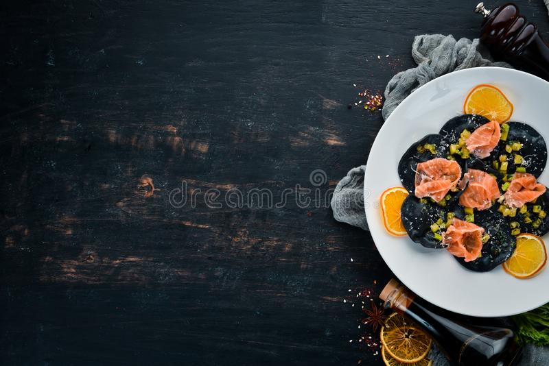 Zwarte ravioli met zalm en parmezaanse kaaskaas stock afbeeldingen