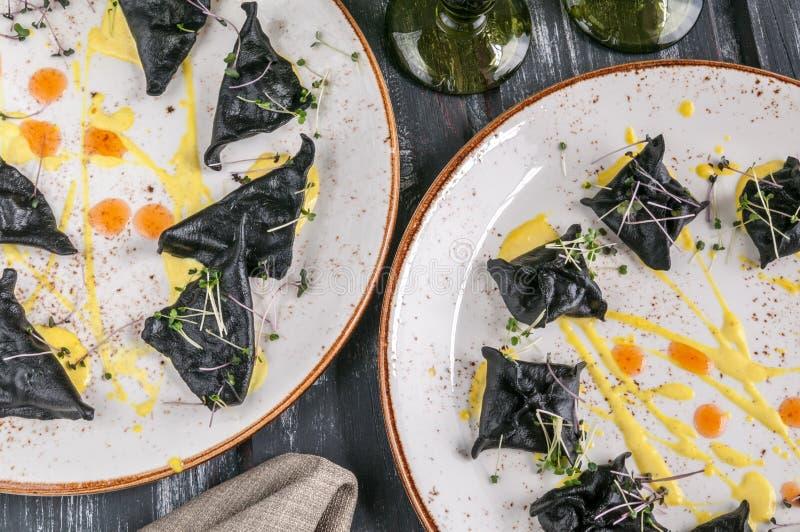 Zwarte ravioli met zeevruchten Op een plaat hoogste mening Op houten zwarte achtergrond stock foto's