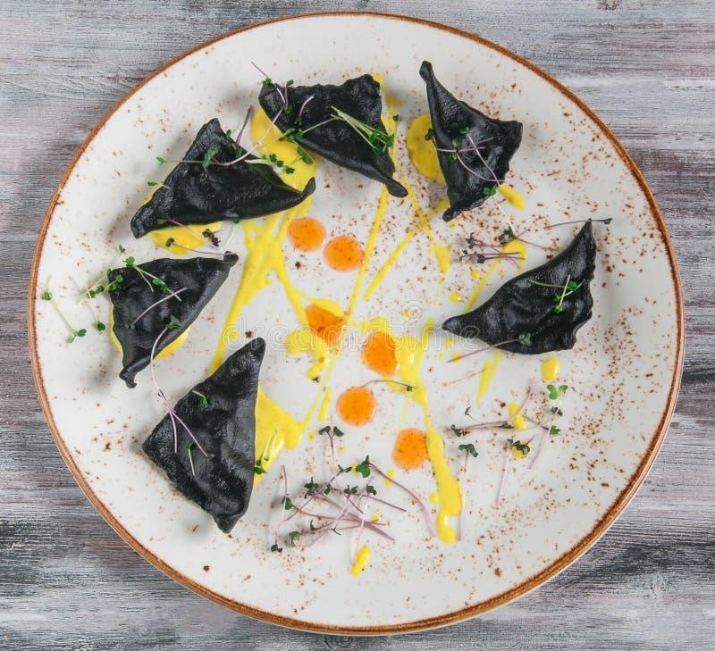 Zwarte ravioli met zeevruchten Op een plaat hoogste mening Op houten grijze achtergrond stock afbeeldingen
