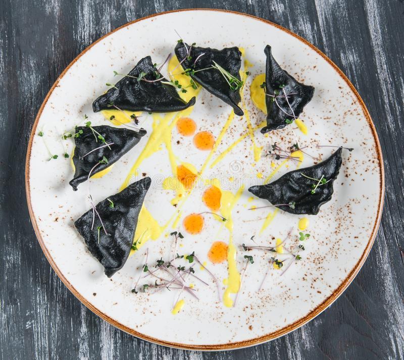Zwarte ravioli met zeevruchten Op een plaat hoogste mening Op houten grijze achtergrond royalty-vrije stock afbeelding