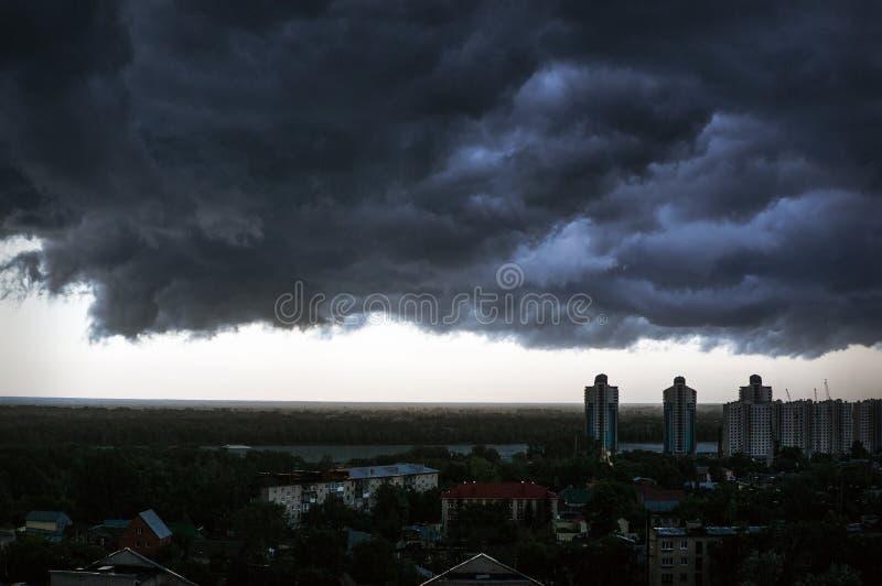 Zwarte regenwolken in hemel boven huizen royalty-vrije stock foto's