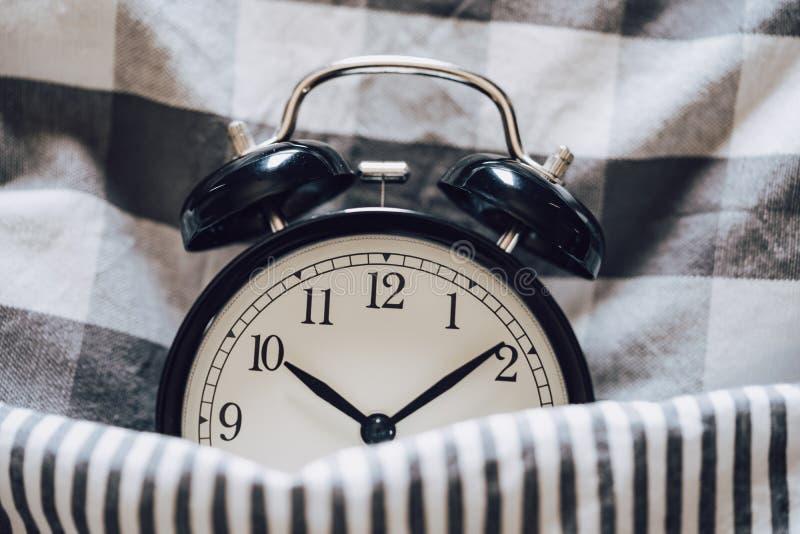 Zwarte retro wekkerslaap op hoofdkussen met algemene metafoor van slapeloosheid, laat op het werk, goed slaap met tijdaftelproced stock afbeelding