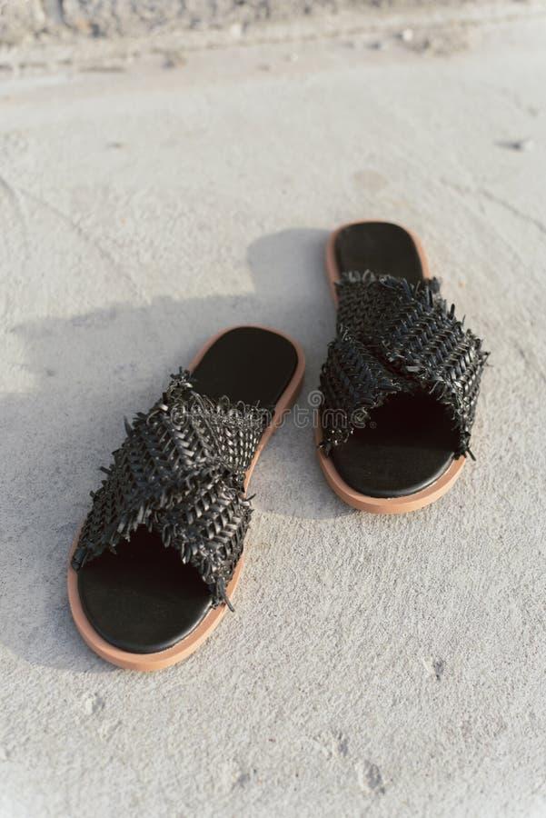 Zwarte rieten schoenen met vlak enig Modieuze de zomerleien zonder benen Modieuze vrouwelijke pantoffels op grijs asfalt met een  stock afbeeldingen