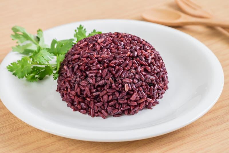 Zwarte rijst die op witte plaat wordt gekookt stock fotografie