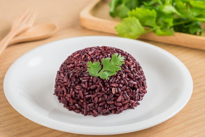 Zwarte rijst die op witte plaat wordt gekookt stock afbeelding
