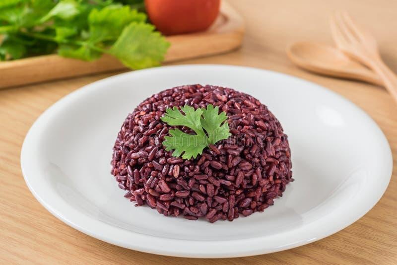 Zwarte rijst die op witte plaat wordt gekookt stock afbeeldingen