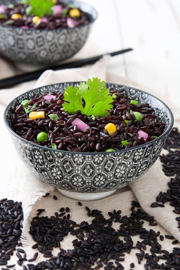 Zwarte rijst in een kom en groenten op witte houten lijst royalty-vrije stock fotografie