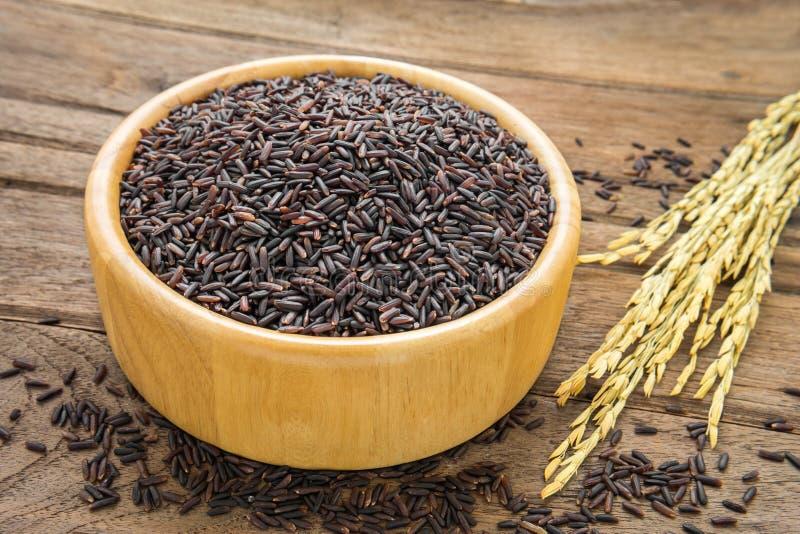 Zwarte rijst in kom op houten lijst stock foto's