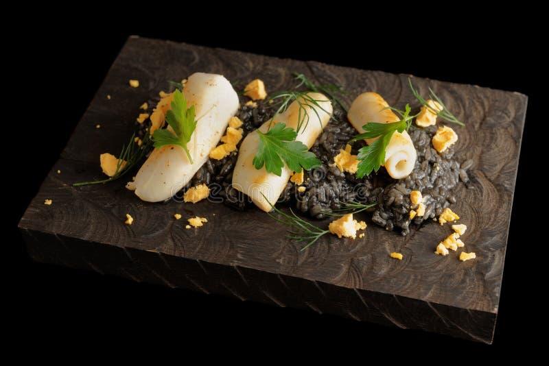 Zwarte risotto van de pijlinktvisinkt met geschroeide calamary stock afbeeldingen