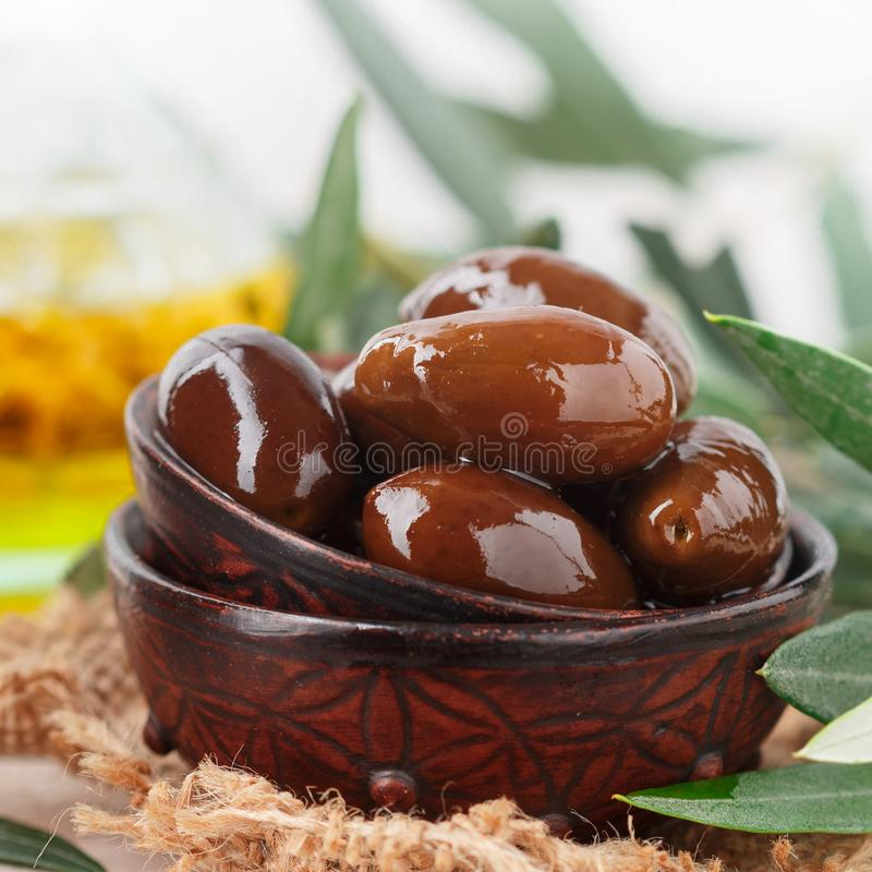 Zwarte rode glanzende olijven van delicatessen de Griekse Kalamata in ceramische kom op houten lijst Olie en takjes Selectieve na royalty-vrije stock afbeelding