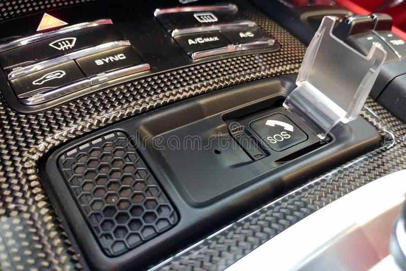 Zwarte S.O.S.knoop met spreker en microfoon in de premiecabine van luxeauto Sluit omhoog van koolstofcontrolebord in autobinnenla stock fotografie