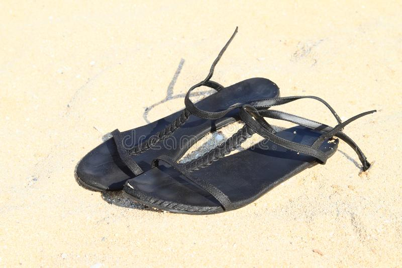 Zwarte sandals op het zand royalty-vrije stock afbeelding