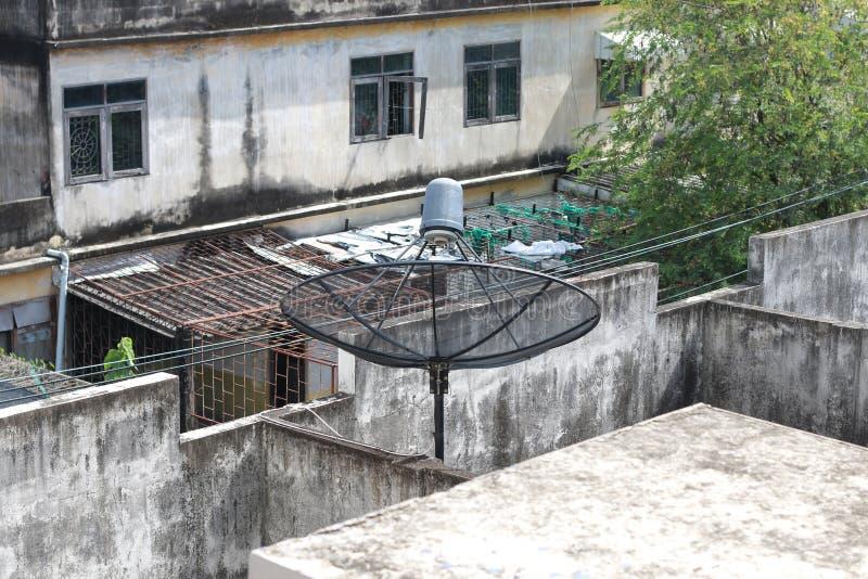 Zwarte satellietschotel en TV-antenne bij oud dorp, parabolische digitale ontvanger voor communicatiegegevens op dak royalty-vrije stock afbeeldingen