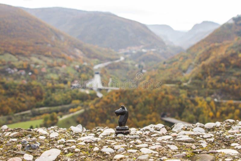 Zwarte schaakridder op de achtergrond van de bergen in de stad van Sarajevo in de herfst In de schaduw gestelde hulpkaart met bel royalty-vrije stock afbeeldingen