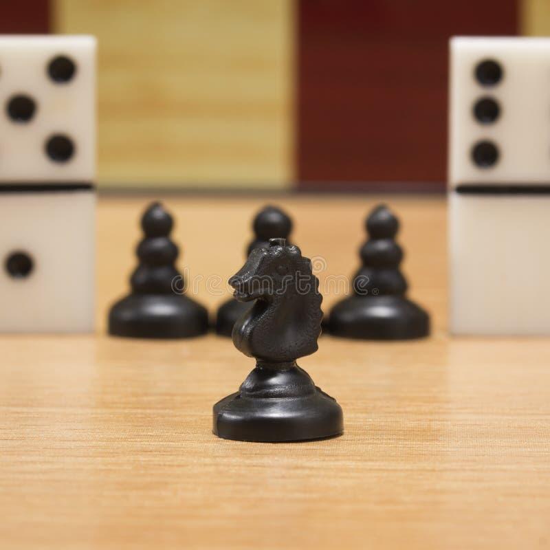Zwarte schaakridder op de achtergrond van panden en domino's royalty-vrije stock foto