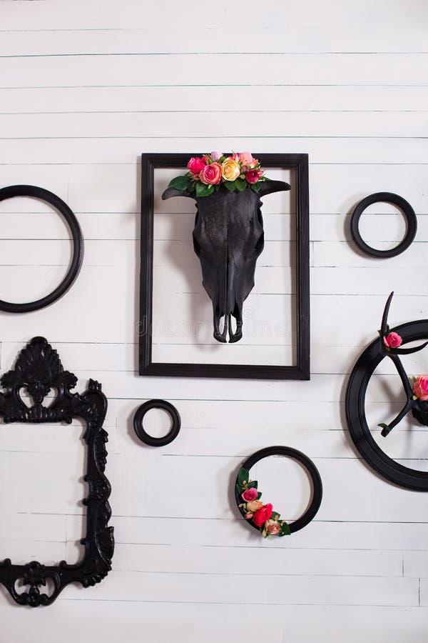 Zwarte schedel van een hert en hoornen op een houten witte muur met lege kaders voor schilderijen Het concept het verfraaien van  stock afbeelding
