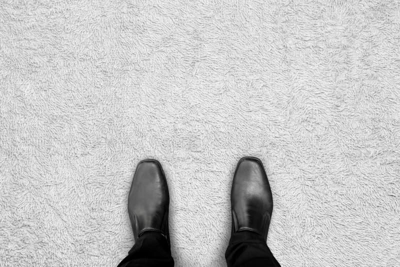 Zwarte schoenen die zich op het tapijt bevinden stock afbeelding