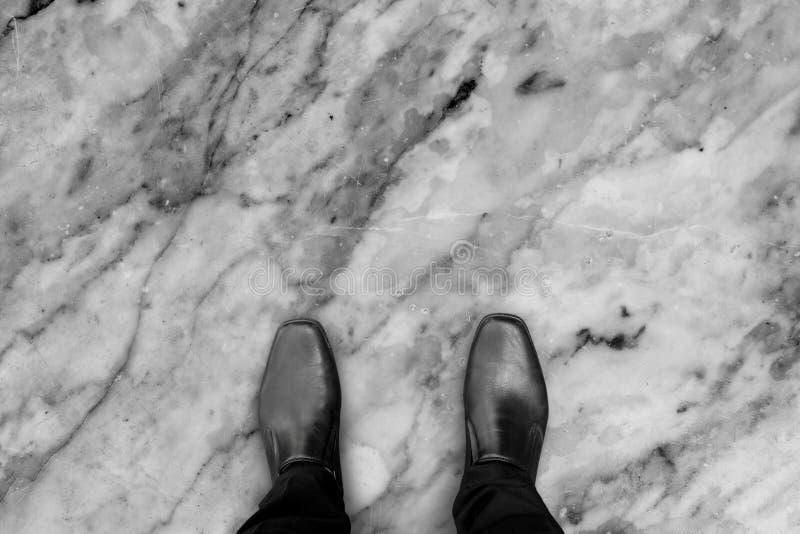 Zwarte schoenen die zich op marmeren steenvloer bevinden stock fotografie