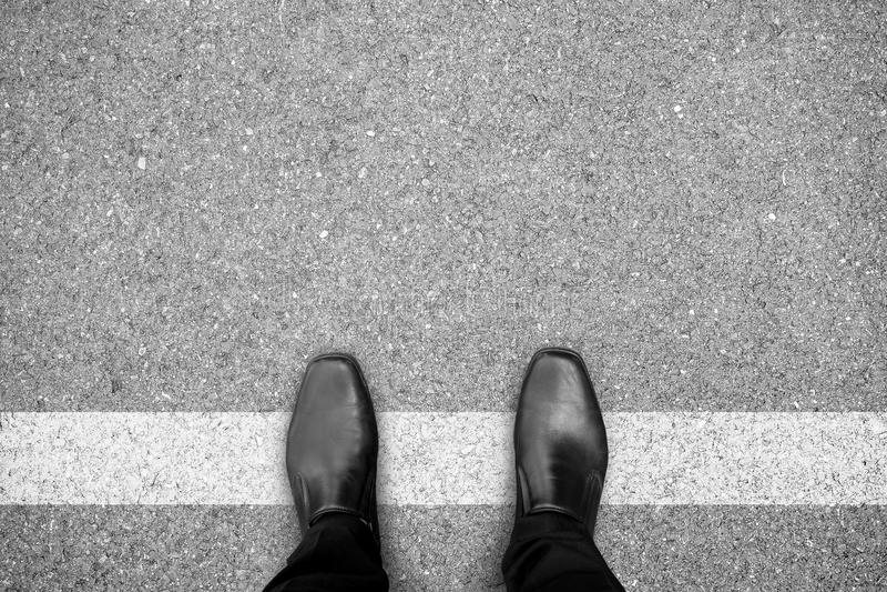 Zwarte schoenen die zich op witte lijn bevinden royalty-vrije stock afbeelding