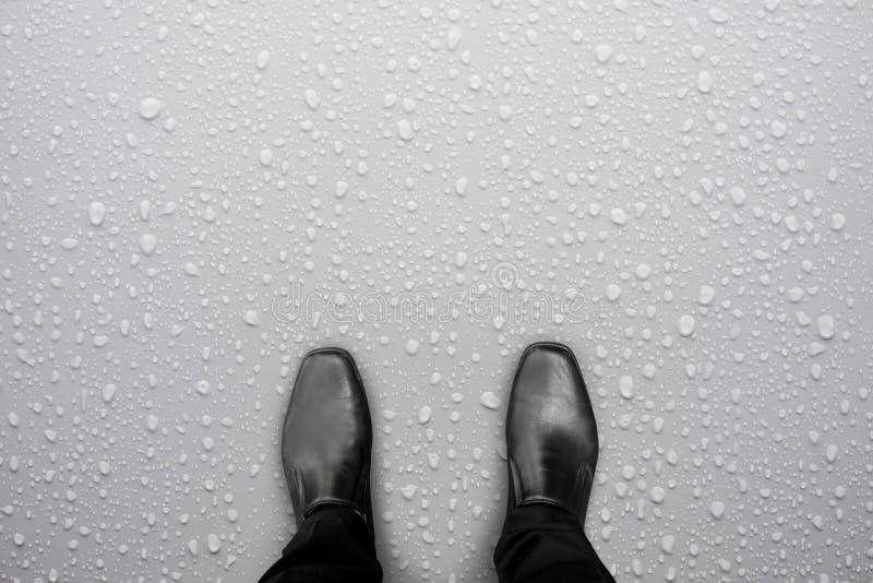 Zwarte schoenen die zich op witte natte vloer bevinden stock afbeelding