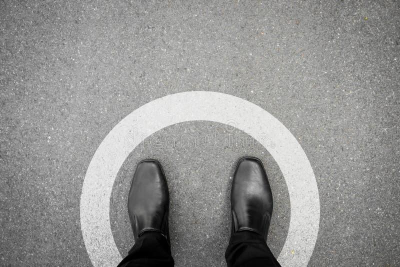 Zwarte schoenen die zich in witte cirkel bevinden stock foto